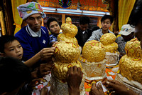 Inle Lake Phaung Daw Oo Paya devotees pasting gold foil on statues covered in gold